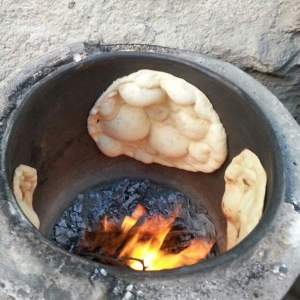 bread cooking on the side walls of a tanour oven
